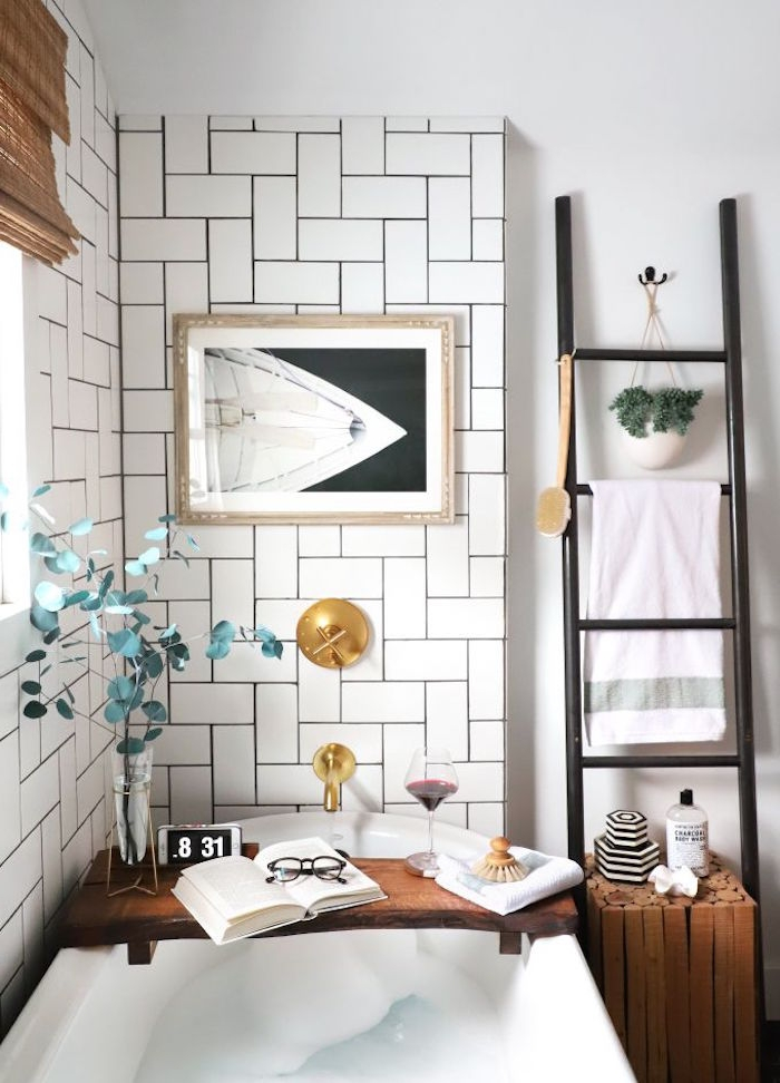 open book and a glass of red wine, reading glasses and a vase, with a green plant, placed on a wooden tray, over a white bathtub, diy bathroom décor, white herringbone subway tiles