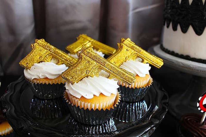 four vanilla cupcakes, with white frosting, topped with small, sparkling gold gun figurines, placed on a black dish, 60th birthday party ideas for men, golden gun themed bond party
