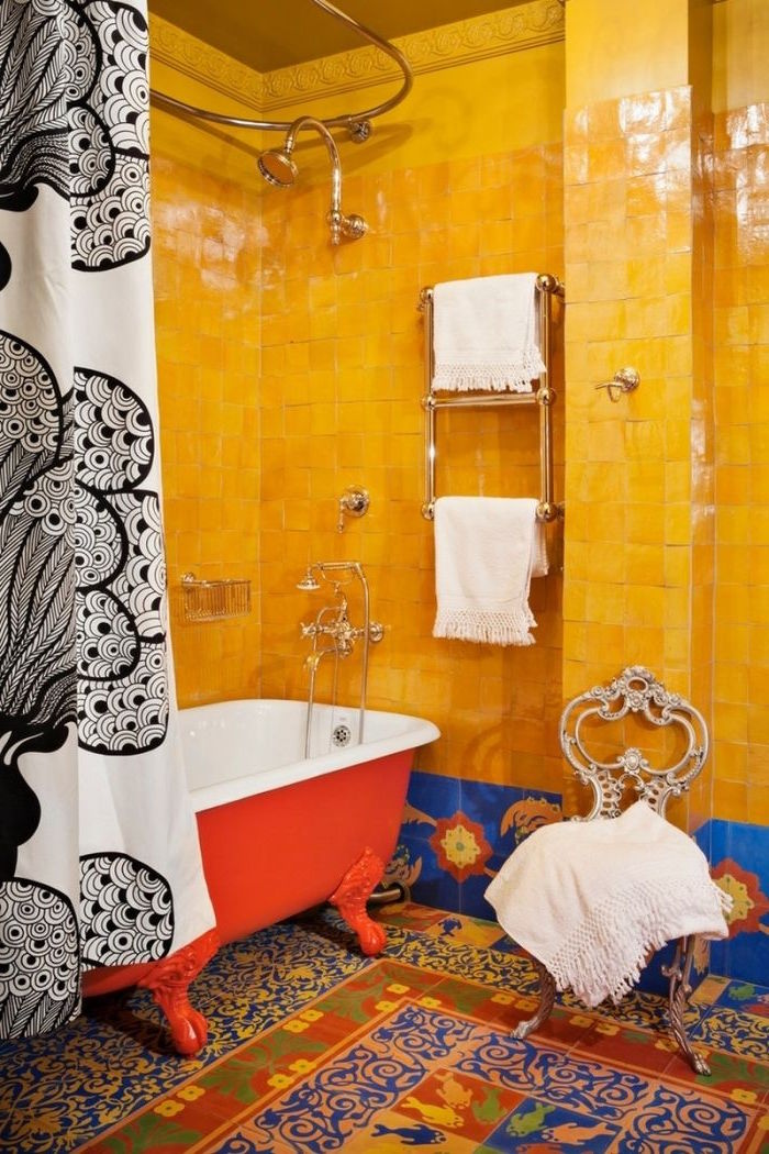 orange tiles with a glossy sheen, in a bathroom with a multicolored tiled floor, a red and white claw-footed tub, and a black and white shower curtain