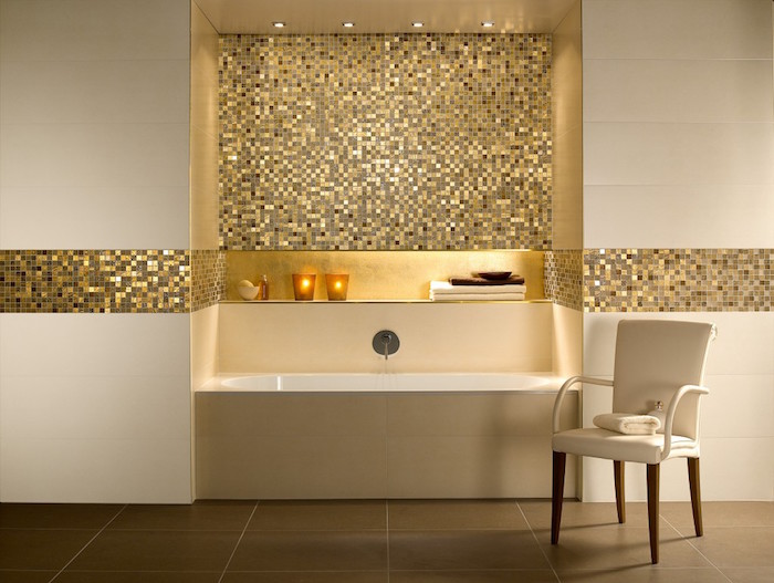 minimalistic bathroom in cream and gold, with a rectangular tub, and a chair, glittering gold mosaic, brown tiled floor