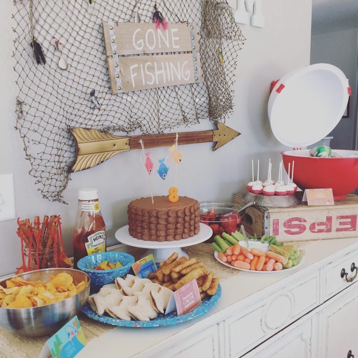 chips sandwiches and other treats, on a table containing a chocolate cake, decorated with fishing themed ornaments, 60th birthday ideas, fishing net and a sign saying gone fishing