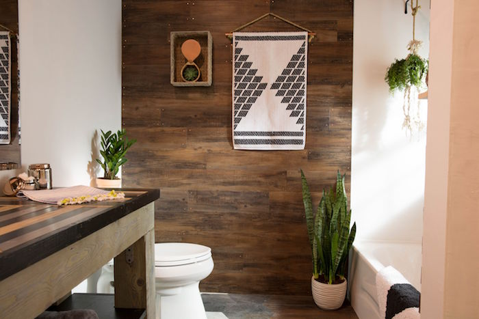 wooden panelling in brown, on one of the walls of a room, with a massive wooden table, a toilet and a bathtub, nice bathrooms, potted plants and a wall decorations