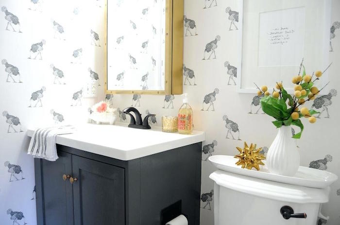 ostrich patterned wallpaper, in white and grey, small bathroom décor, black cupboard with an inbuilt white sink, white toilet and various decorations