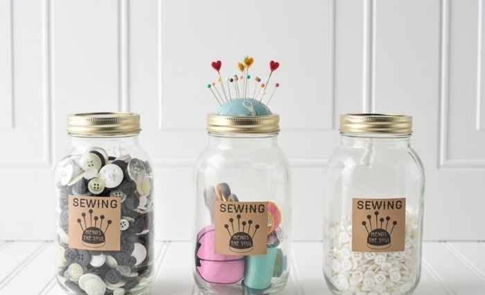 sewing accessories organizers, made from mason jars, with beige labels, two containing buttons, and one thread and pins