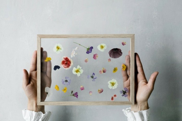 pressed flowers inside a glass panel, with a light wooden frame, cute birthday ideas, held by two hands, in frilly white sleeves