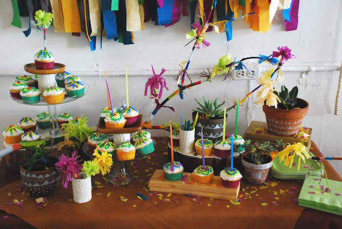 confetti and paper garlands in different colors, decorating a table, covered with multicolored cupcakes 60th birthday color, brown tablecloths and potted succulents
