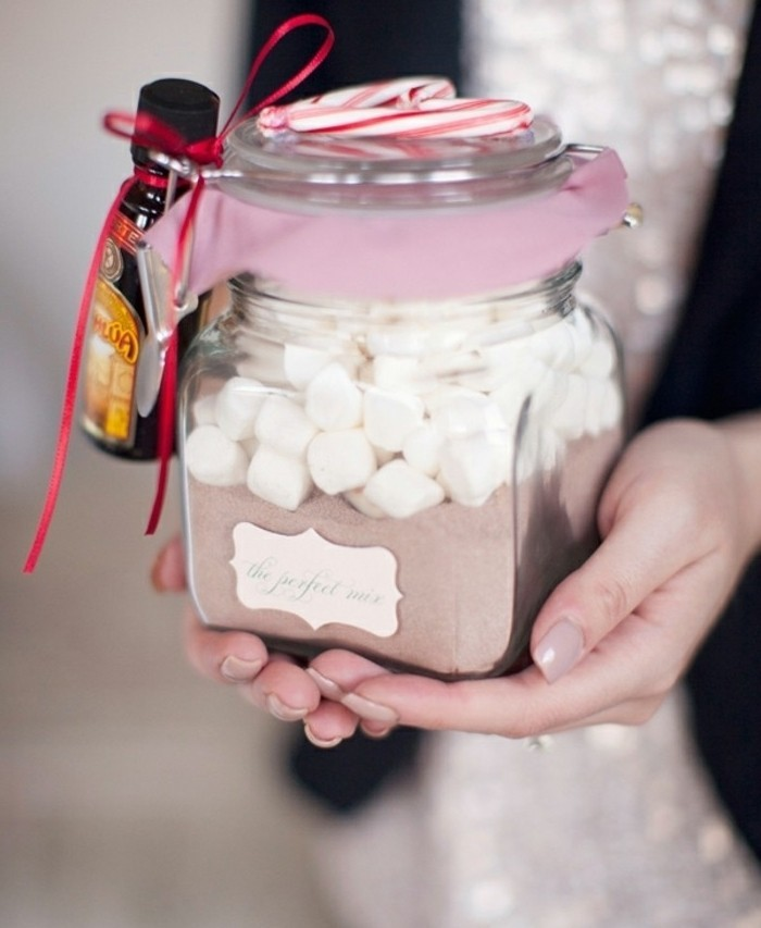 jar with a snap lid, containing cocoa powder, and white marshmallows, cute birthday ideas, small bottle of rum tied to it, two peppermint canes on top of the lid