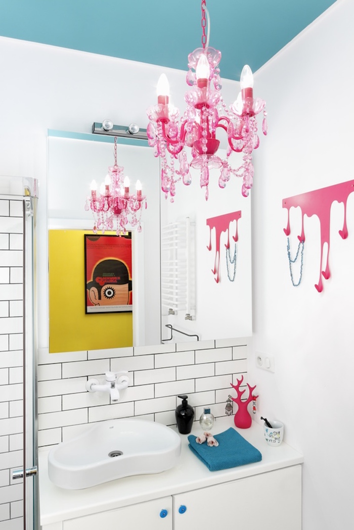 pop art inspired room, with a teal blue ceiling, and a hot pink chandelier, white walls partially decorated with white subway tiles, and decorations in hot pink and blue, small bathroom decorating ideas, a clockwork orange poster