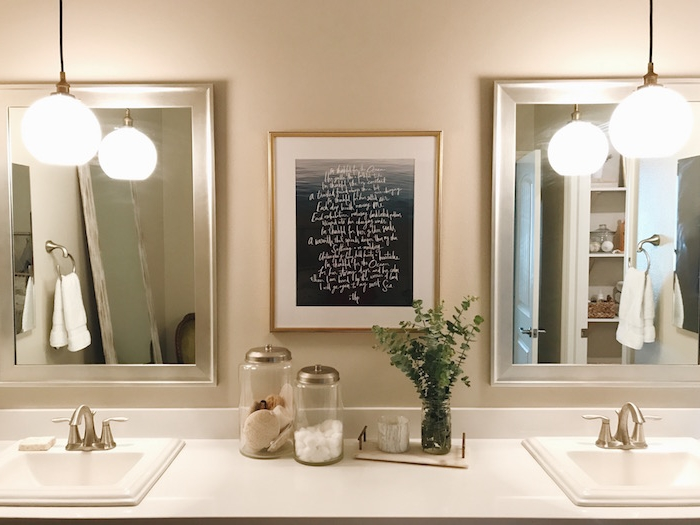 symmetrical bathroom setup, featuring two sinks, two lit lamps, and two mirrors, nice bathrooms, framed poster with writing in white, and two jars with toiletries