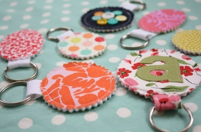 seven multicolored keyrings, made from patterned fabric, in round shapes, attached to metal rings, homemade gift ideas