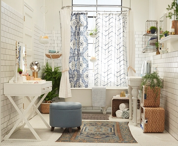 subway tiles in white, on the walls of a bright room, decorated with potted plants, and several shower curtains, rugs and white furniture, bathroom decorating ideas on a budget