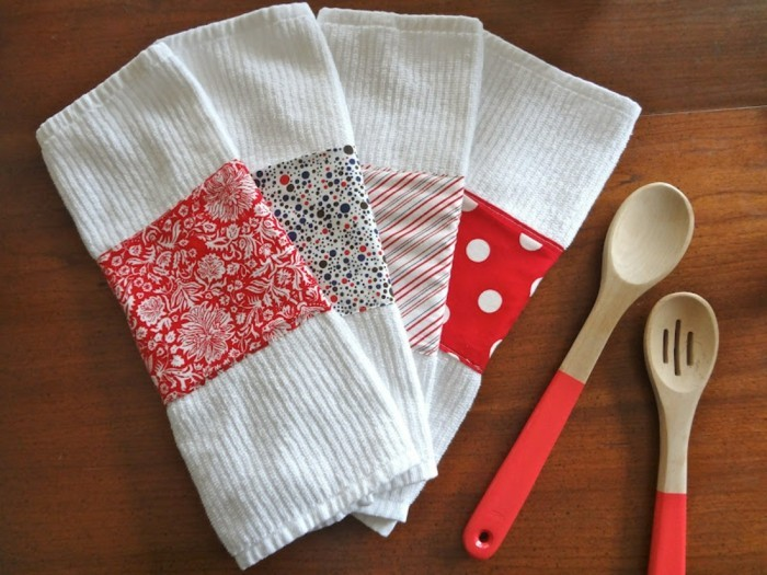 towels in white, decorated with patterned pieces of fabric, in red and white, cute birthday ideas, two wooden spoons with red handles