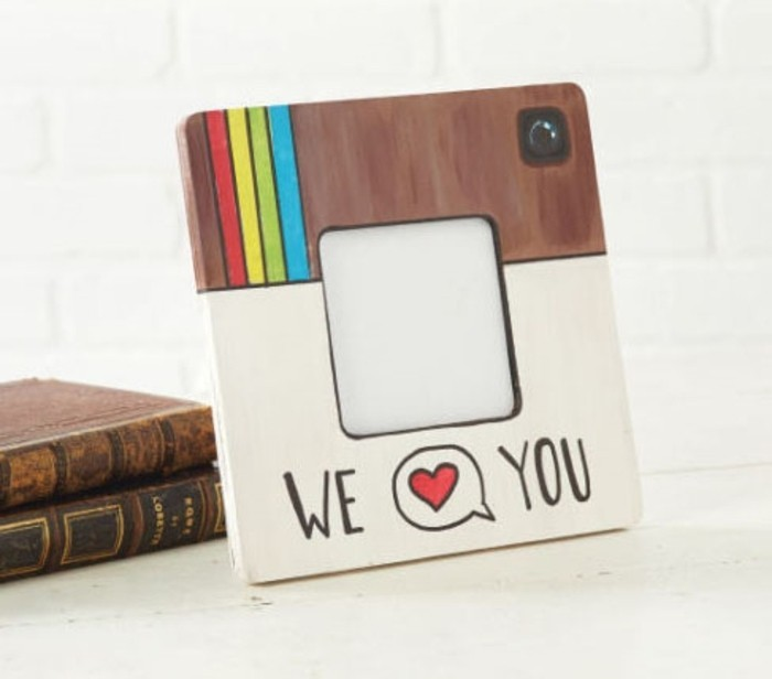 square frame, painted to look like the instagram logo, with the words we and you, divided by a speech bubble, containing a heart symbol
