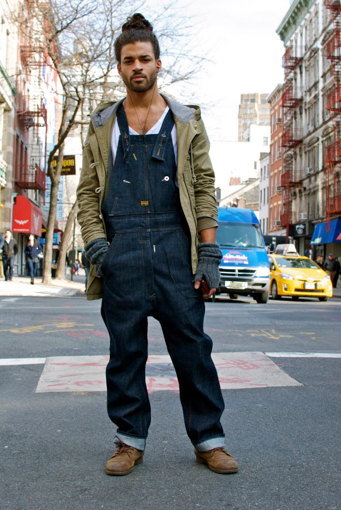 man bun worn by a young man, with beard and mustache, wearing baggy retro denim overalls, worker's boots and a khaki green parka, 90s inspired outfits, over a white t-shirt
