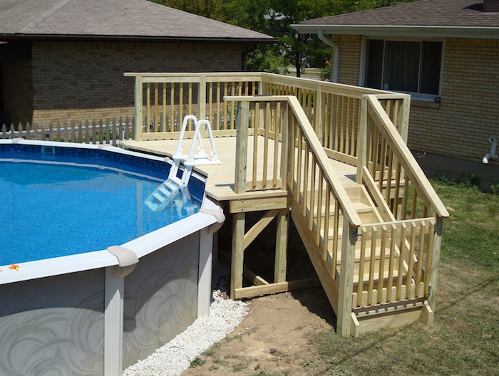 staircase and a small deck, made from pale, cream-colored wood, next to a garden pool, small above ground pools, houses in the background