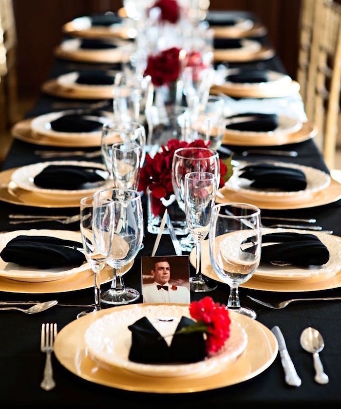 napkins in black and white, folded to look like tuxedos, on a long black table, set for dinner, 60th birthday color, white and black theme, decorated with red flowers, and a photo of sean connery