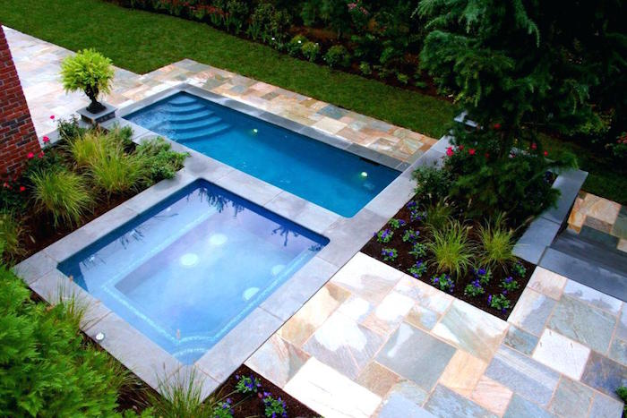 horizontal and vertical small pools, in a garden with green grass, marble-like tiles, and various shrubs
