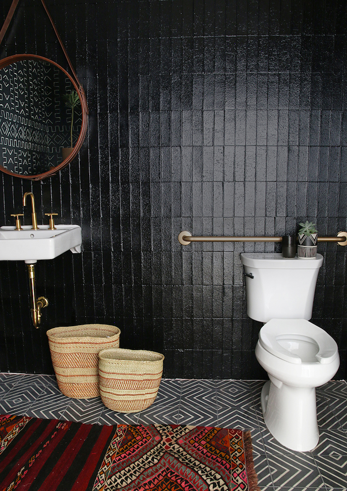 jet black wall tiles, in a room with a black and white tiled floor, containing a white ceramic toilet bowl, and a matching sink, bathroom wall decor ideas, multi-coloured rug with a tribal pattern