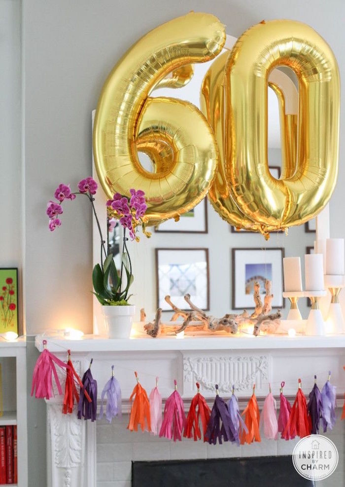 large balloons in gold, shaped like the numbers 6 and 0, near a mantelpiece, decorated with streamers in pink, red and violet