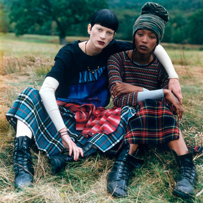 models dressed in retro outfits, sitting on a grassy area, 90s clothes womens, lace up ankle boots, tartan skirts and colorful tops