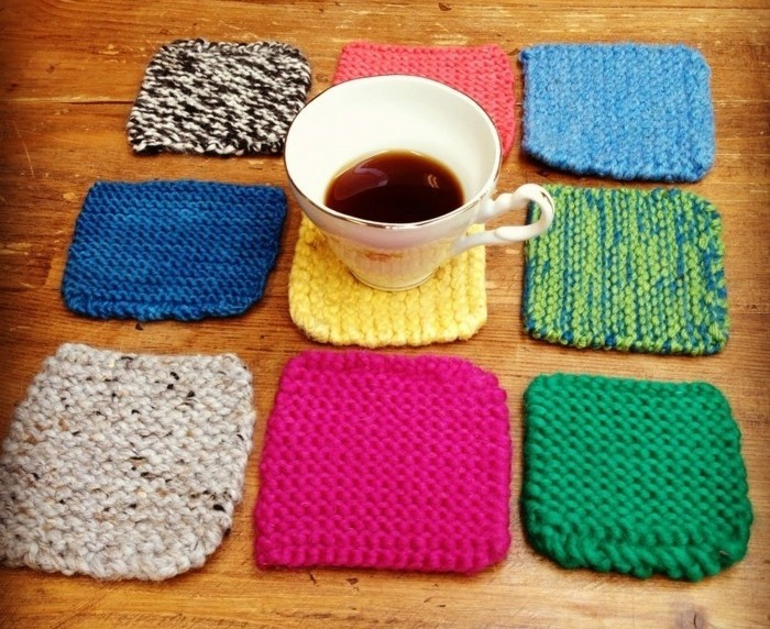 nine square knitted coasters, in navy blue and teal, pink and yellow, green and red, and mixed colors, last minute birthday gifts, half-filled teacup on one of them