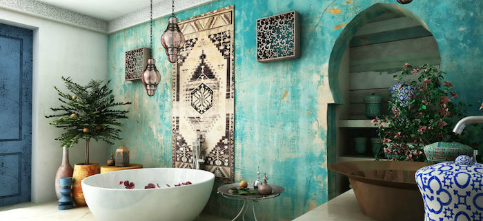 unevenly painted turquoise accent wall, inside a moroccan-style bathroom, containing a round bathtub, a small indoor tree, and lots of decorative items