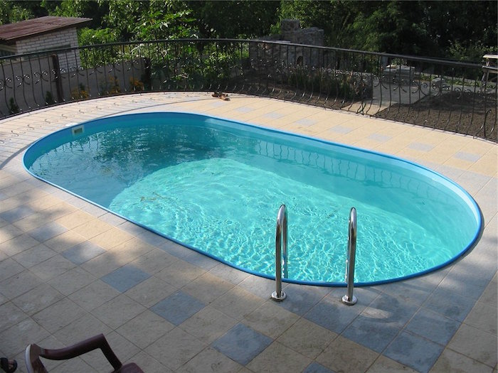 small inground swimming pools, blue oval shaped pool, filled with water, on a terrace with black metal fence