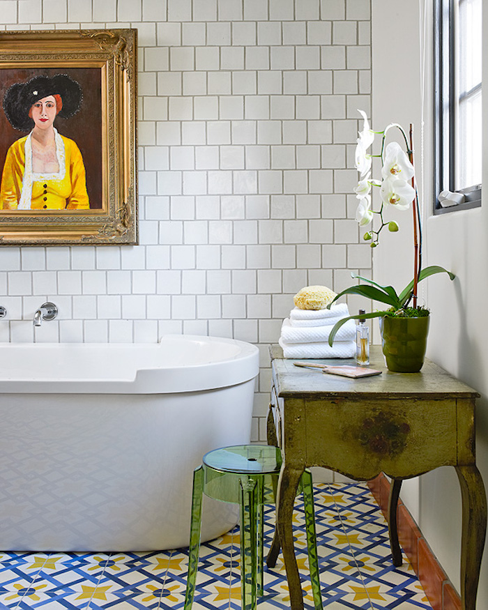 diy bathroom décor, white subway wall tiles, and colorful blue, yellow and white floor tiles, in a room containing a white tub, a framed painting, and boho chic furniture