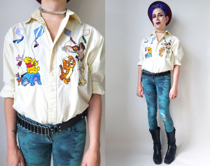 winnie-the-pooh characters embroidered on a pale yellow shirt, worn by a woman with violet hair, wearing violet lipstick, 90s halloween costumes, black boots and skinny jeans, decorated with paint