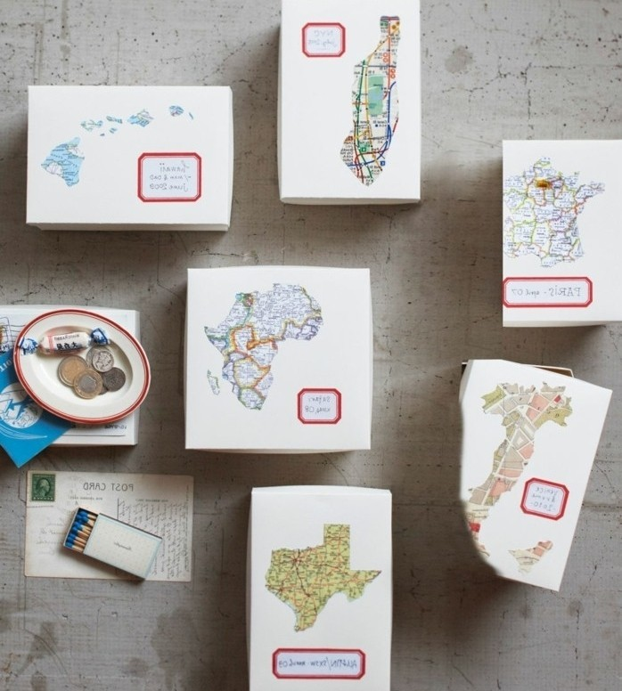 six boxes made of card, each decorated with a different map, and a small, red-rimmed label, handmade gift ideas