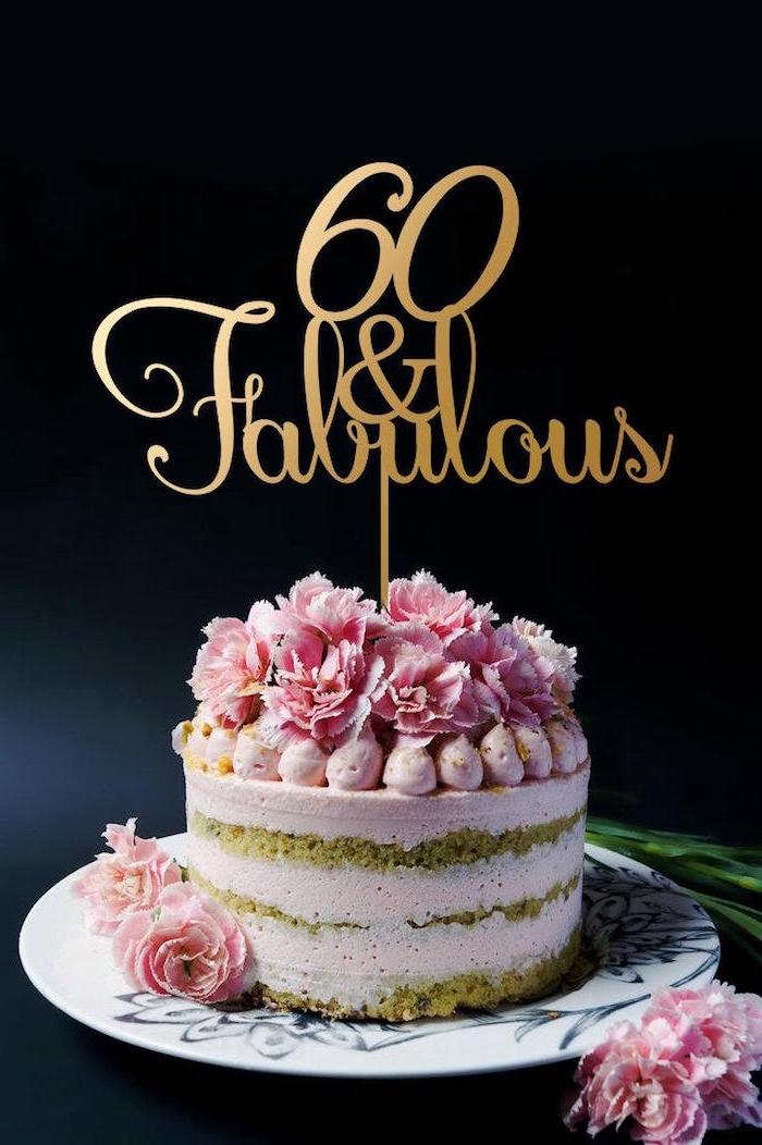 fresh pink flowers, on a creamy pale pink cake, decorated with a gold topper, bearing the inscription, 60 and fabulous