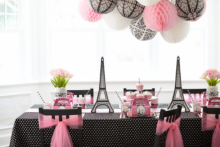 pink and black table setup, decorated with eiffel tower figurines, and two bouquets of pale pink flowers, 60th birthday color, parisian party theme