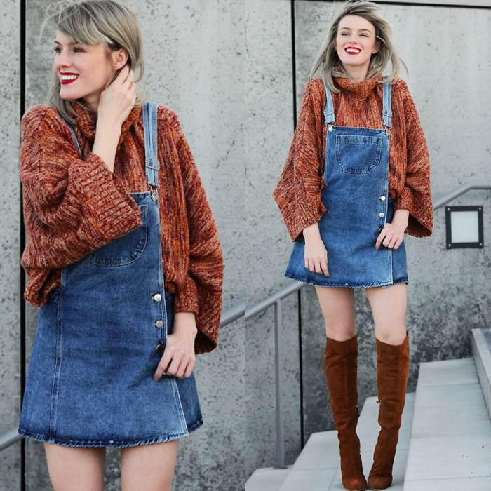 dungaree dress made from denim, with side buttoning, worn over a bulky, brick red turtleneck jumper, by a smiling blonde woman, with knee-high brown suede boots