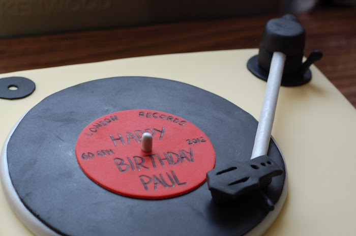 party cake shaped like a vintage record player, with a black and red vinyl record, all made from colorful fondant, happy 60th birthday paul, written In black on top