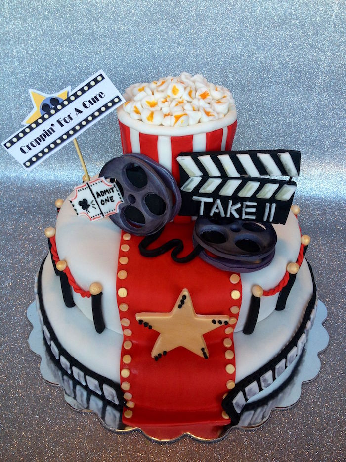picture house-themed party cake, white with a red carpet detail, gold buttons and a large gold star, 60th birthday decorations, clapboard and popcorn, ticket and film reels