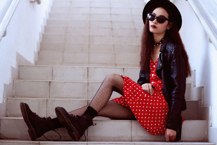 fishnet tights and black combat boots, worn with a red mini dress, with white polka dots, and a black leather jacket, by woman with sunglasses and a hat