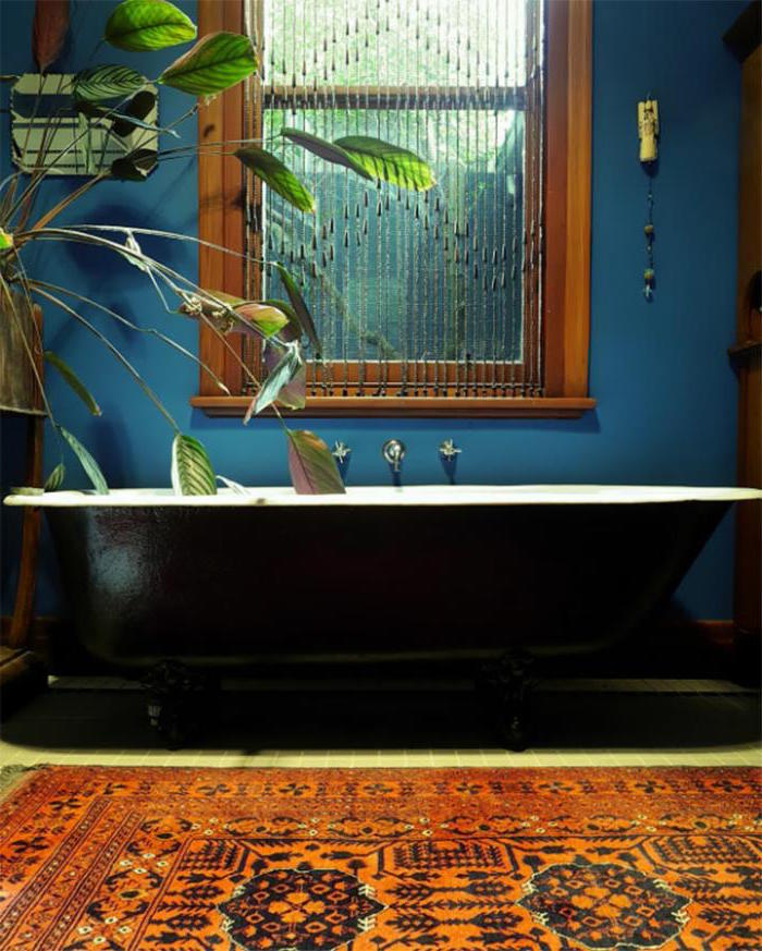 black and white tub, in a room with blue walls, containing a window with a brown frame, a potted plant, and a kilim rug in red, with a dark oriental pattern, diy bathroom