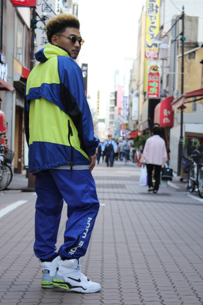 track suit in vintage style, blue and yellow, with black details and a hood, 90s halloween costumes, worn by a man with white, nike high tops, standing on a city street