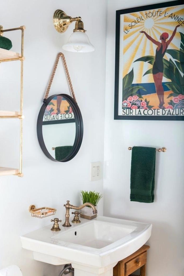 vintage brass faucet, on a white sink, in a room with white walls, decorated with a framed poster, a round mirror, a gold lamp, and other items, small bathroom décor, gold metal shelves