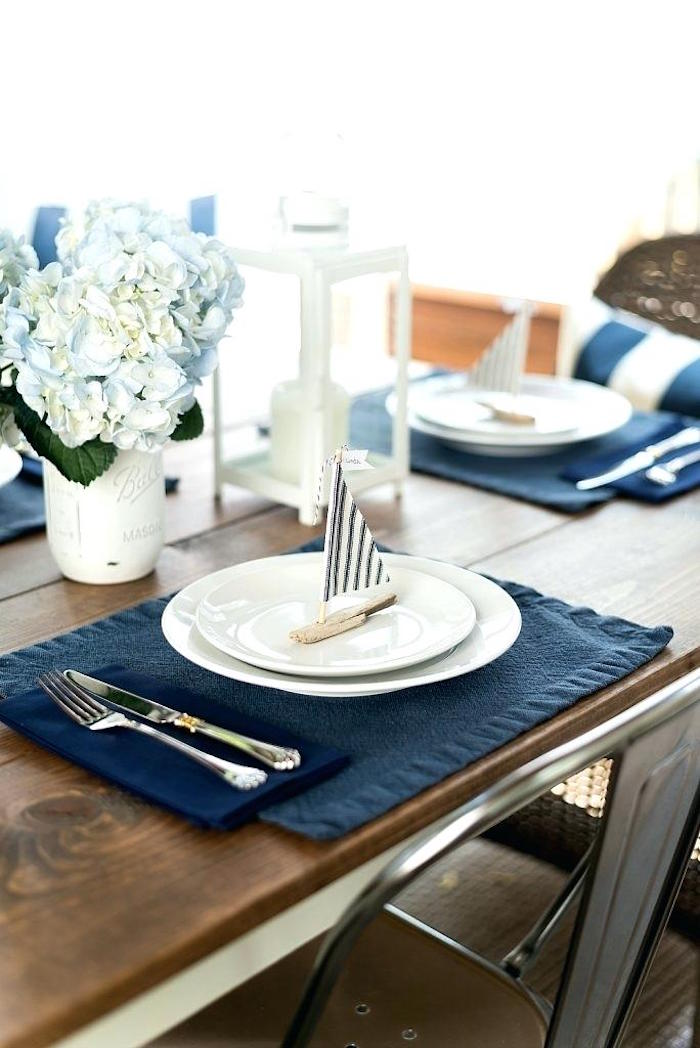 nautical table set up, in navy blue and white, 60th birthday party ideas for men, two white plates, containing a small place holder, shaped like sailing boat
