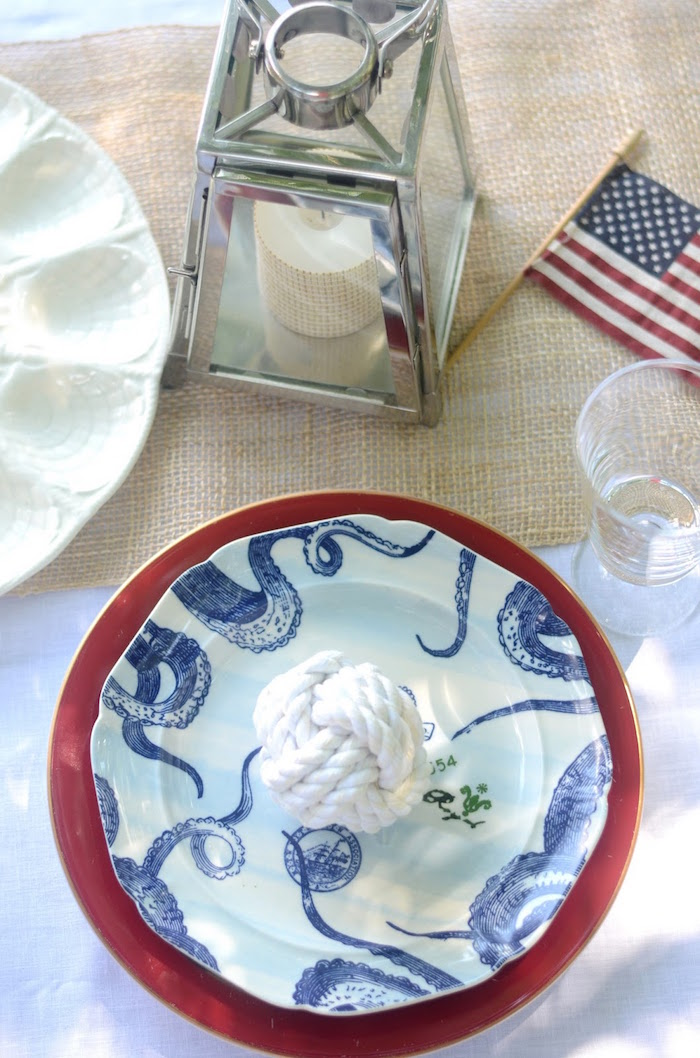 lantern made of glass, and containing candle, and a small american flag, near near a white sailor's knot, placed on a blue nautical plate, on top of a red dish, 60th birthday ideas, sea inspired setup