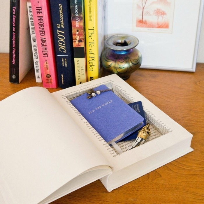 book with a secret compartment, containing various small items, inexpensive thank you gift ideas, placed on a desk, near other books