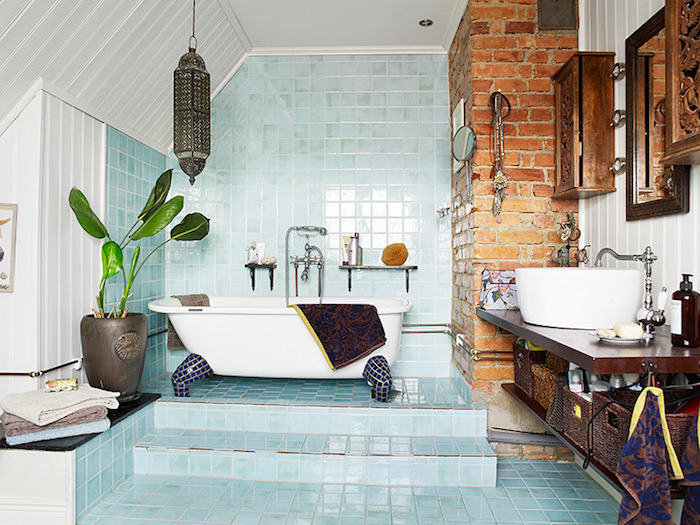 light blue tiles, and white panelling, inside a bright bathroom, containing a tub, a wooden counter with a sink, brickwork detail and engraved wooden cupboards