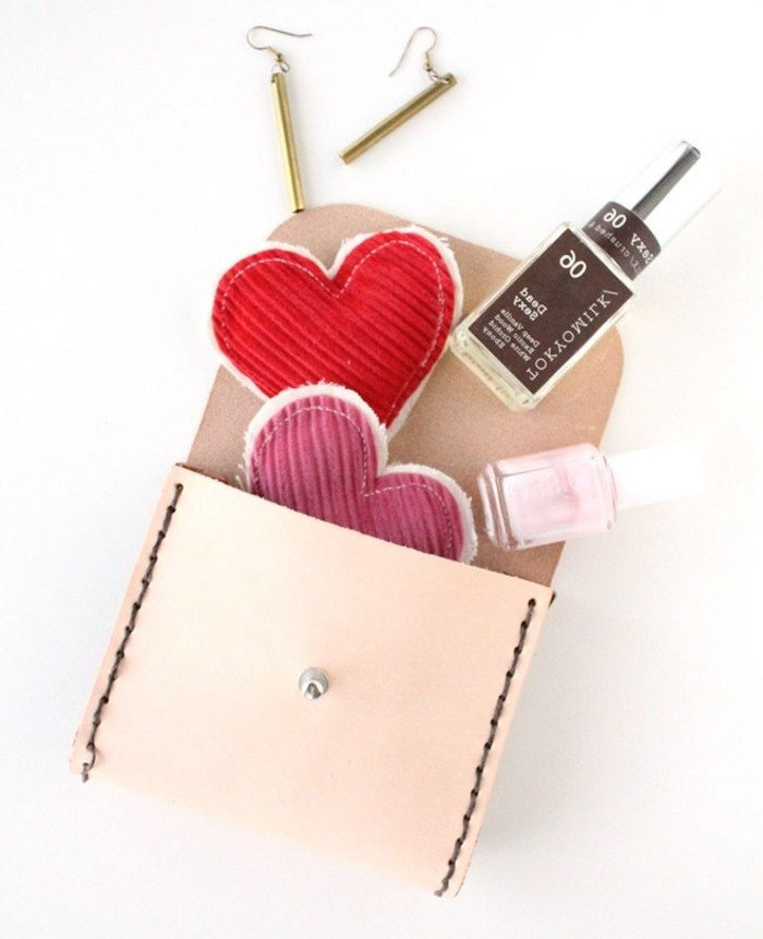 cute birthday ideas, cream leather purse, opened to reveal two bottles of nail polish, two fabric heart ornaments, in red and pink, and a pair of gold earrings