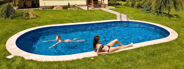 woman sunbathing next to an oval pool, and a little girl swimming inside, small backyard pool ideas, garden with green grass, and a house nearby