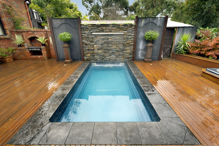symmetrical set up, with a rectangular pool, surrounded by a small column, with a green plant, on each side, backyards with pools, wet wooden planks covering the ground
