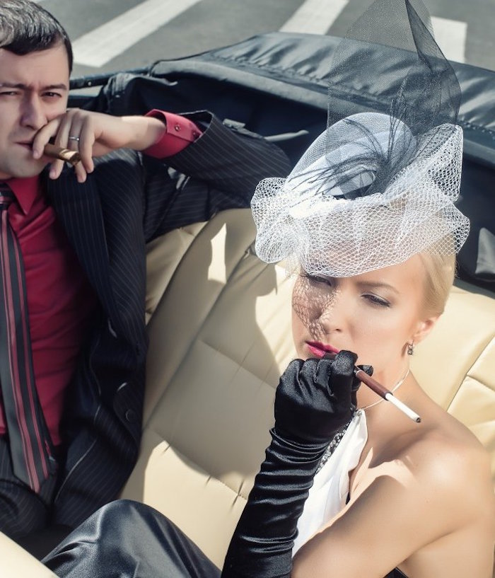 tulle hat in white and black, worn by a woman in black and white dress, smoking a cigarette, great gatsby costumes, in an antique car, next to a man smoking a cigar