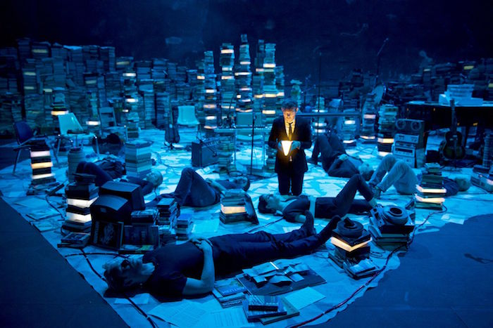kneeling man in a business suit, holding a glowing book, more men lying on the grown around him, amid stacks of books, bathed in blue light
