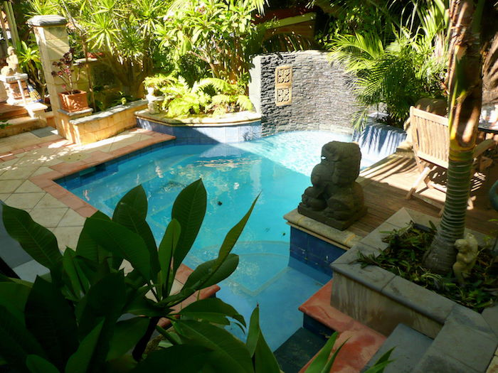 cool backyards, angular pool surrounded by greenery, with a lion statue made of stone, beige and orange tiles on the ground