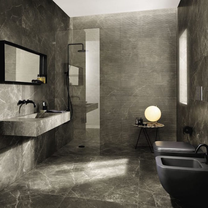 pewter grey room, with stone effect walls and floor, containing a shower, with a clear glass divider, a massive stone sink, with a black faucet, near a mirror in a black frame, dark grey toilet, and matching bidet, modern bathroom ideas